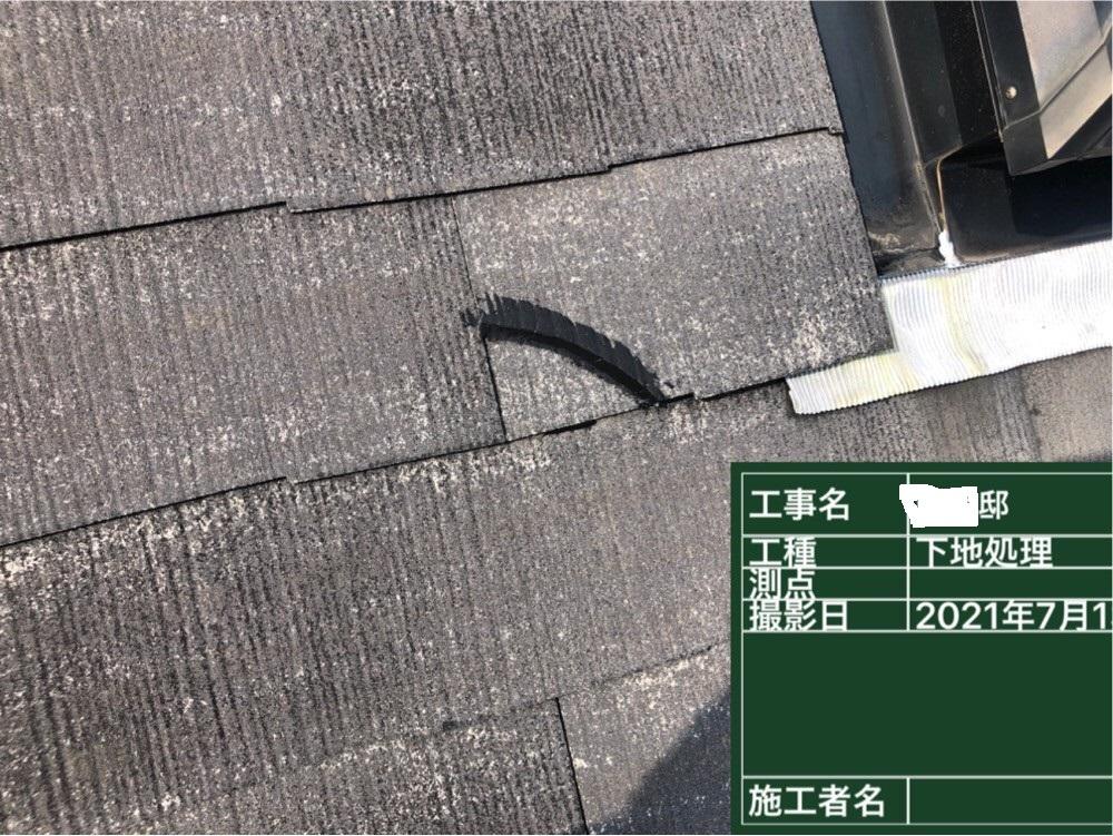 屋根塗装前にひび割れたスレート屋根を補修している様子
