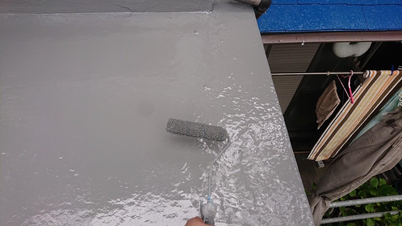 雨漏り修理での防水工事の仕上げとしてトップコートを塗っている様子