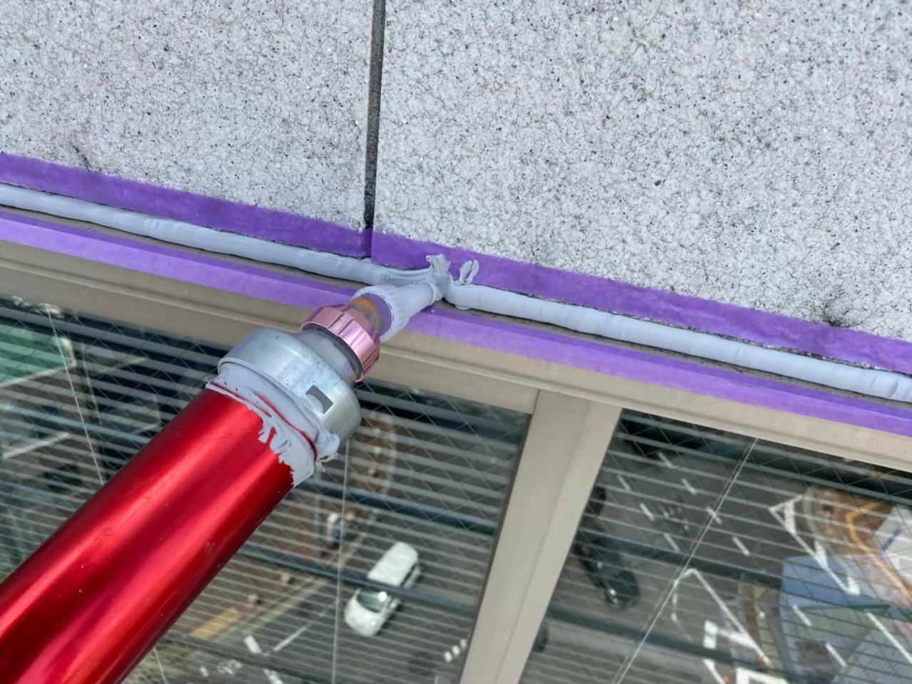 神戸市中央区でのコーキング打ち替え工事でコーキングを流している様子