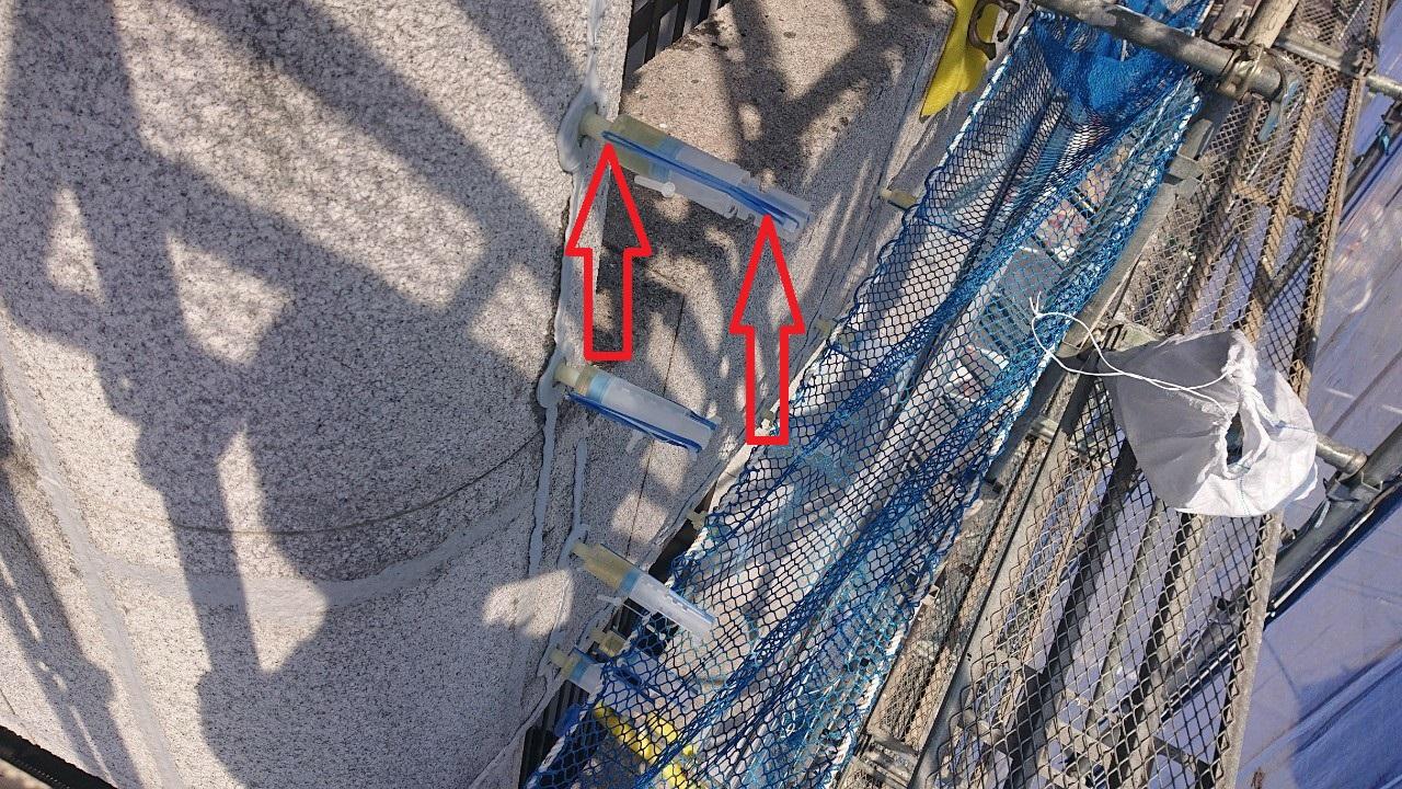 神戸市中央区の外壁補修で輪ゴムを用いて低圧注入している様子