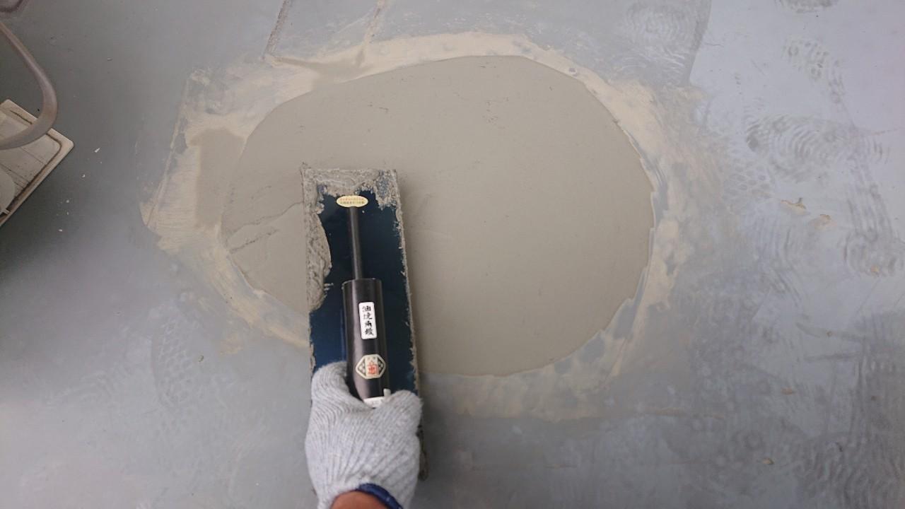 ベランダ床の膨れていた部分を左官で補修している様子