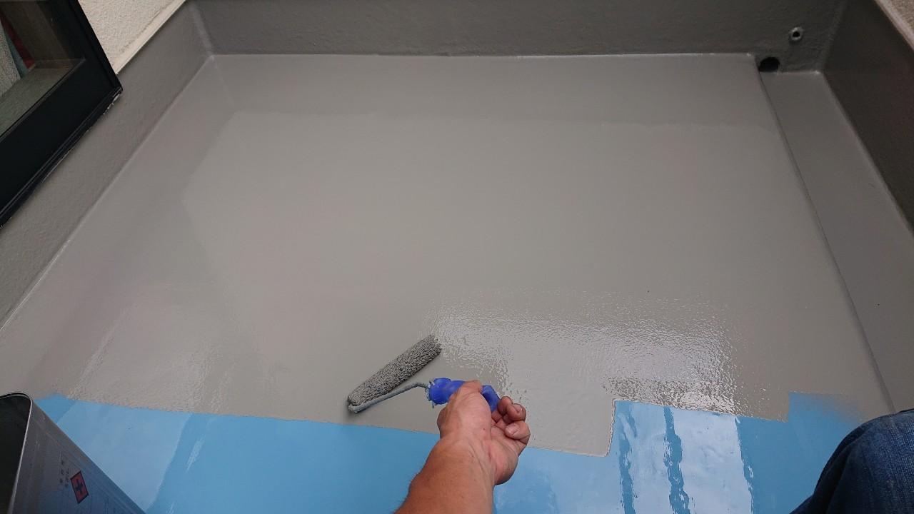 神戸市北区のベランダ防水工事でトップコートを塗っている様子