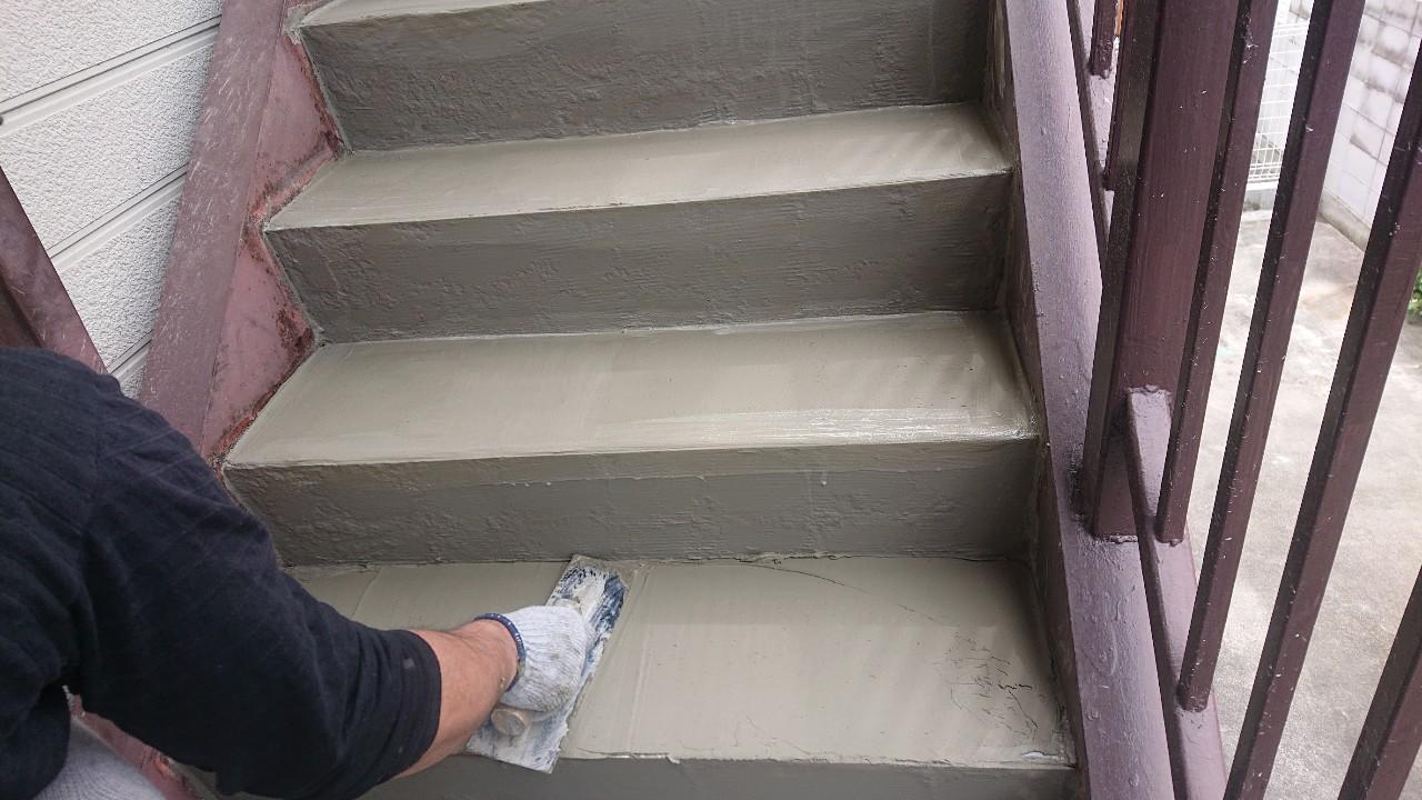 経年劣化した外部階段にセメントを塗っている様子