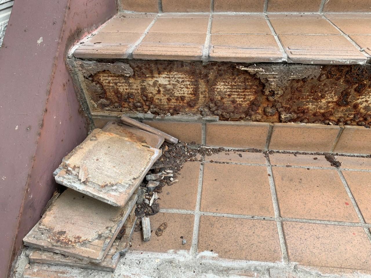 経年劣化で外部階段のタイルが剥がれている様子