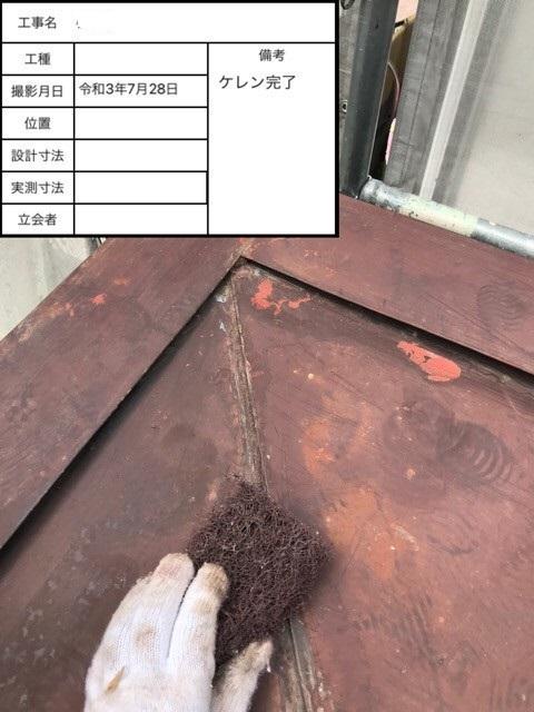 錆び付いたトタン屋根を塗装する前にケレンしている様子
