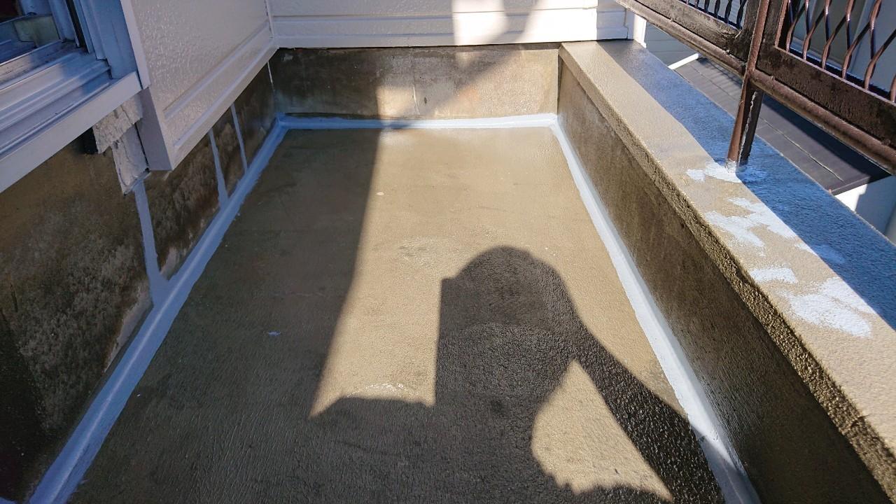 播磨町での雨漏り修理でひび割れたベランダ床にコーキングで補修している様子
