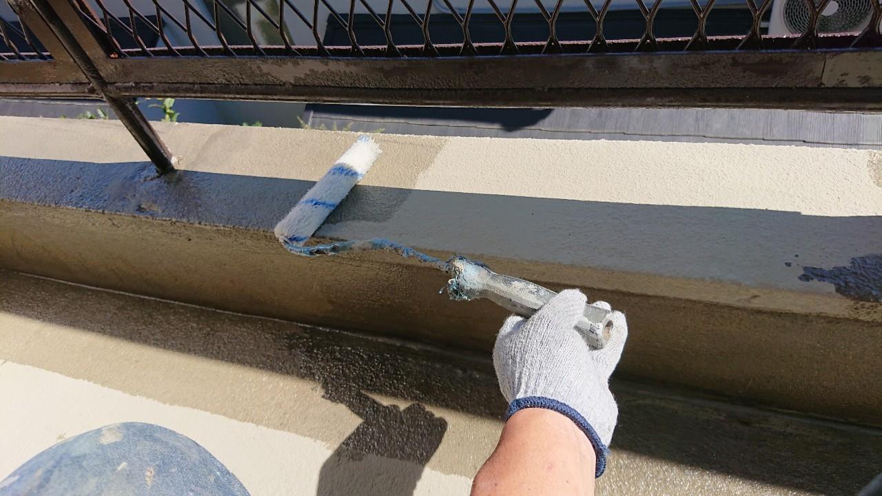 雨漏り修理でひび割れたベランダ床に防水工事を行うためプライマーを塗っている様子