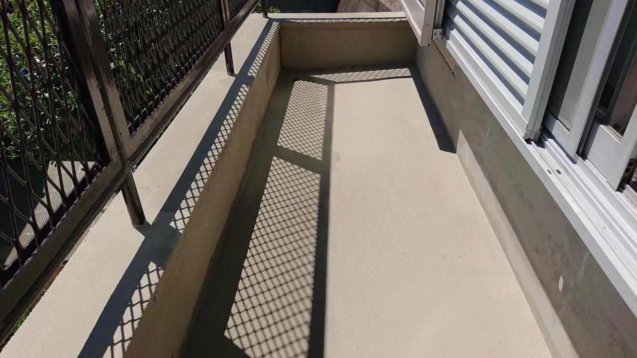 播磨町でのベランダ防水工事でひび割れたベランダ床にセメントを塗った様子