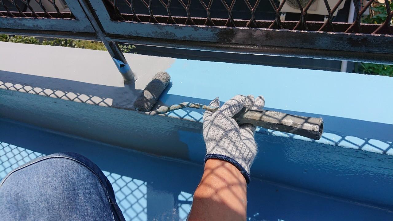 ひび割れたベランダ床に防水工事の仕上げとしてトップコートを塗っている様子