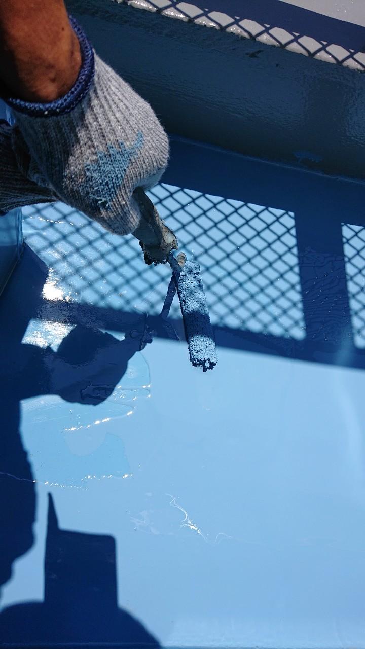 雨漏り修理でひび割れたベランダ床にウレタン防水を中塗りしている様子