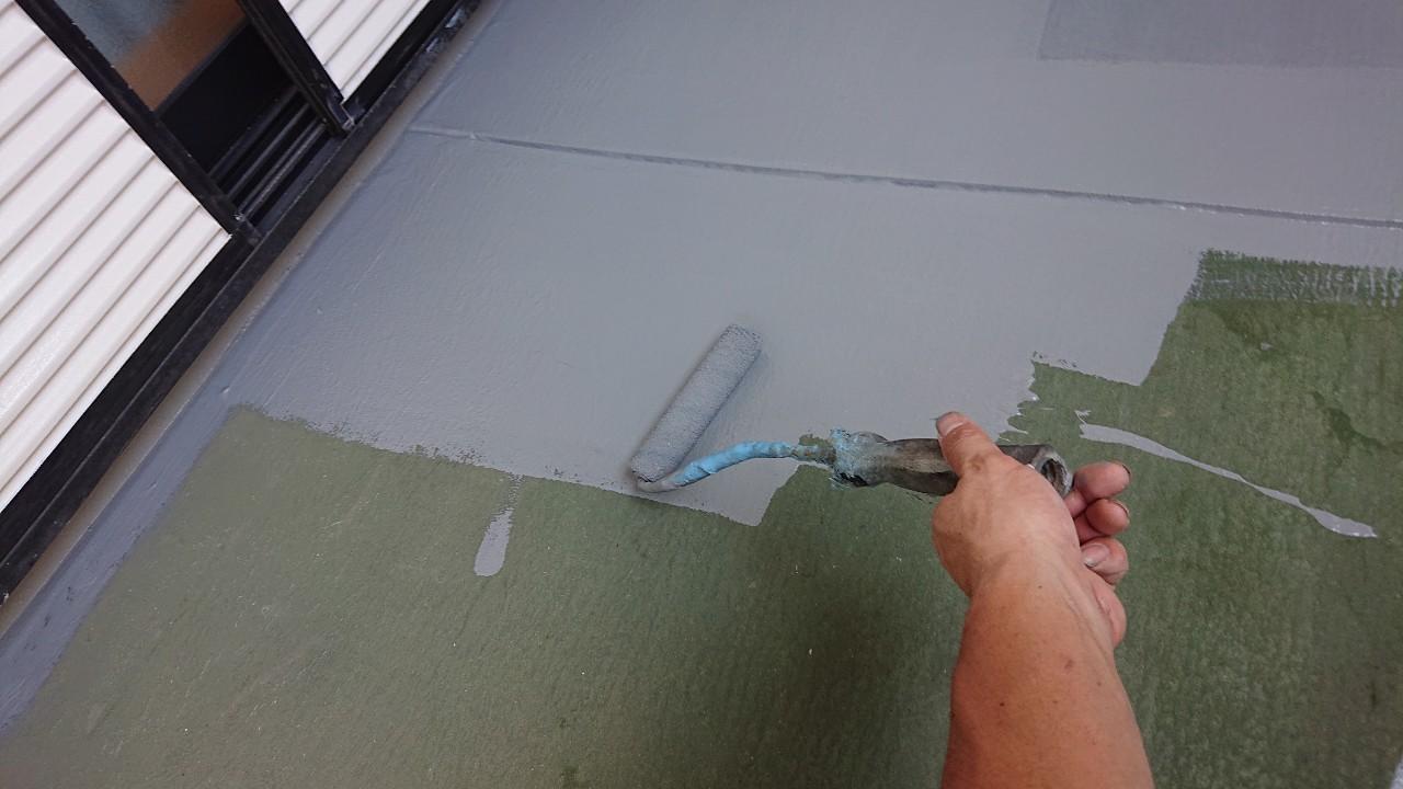 ベランダ床のメンテナンスでローラーを使用してトップコートを塗っている様子