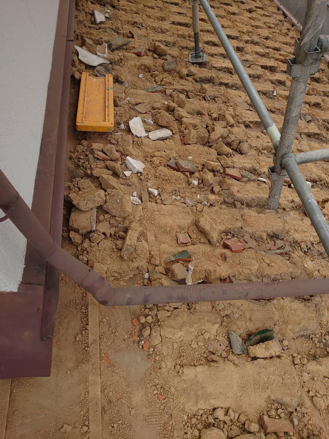 屋根葺き替え工事で瓦屋根の下の土を撤去している様子