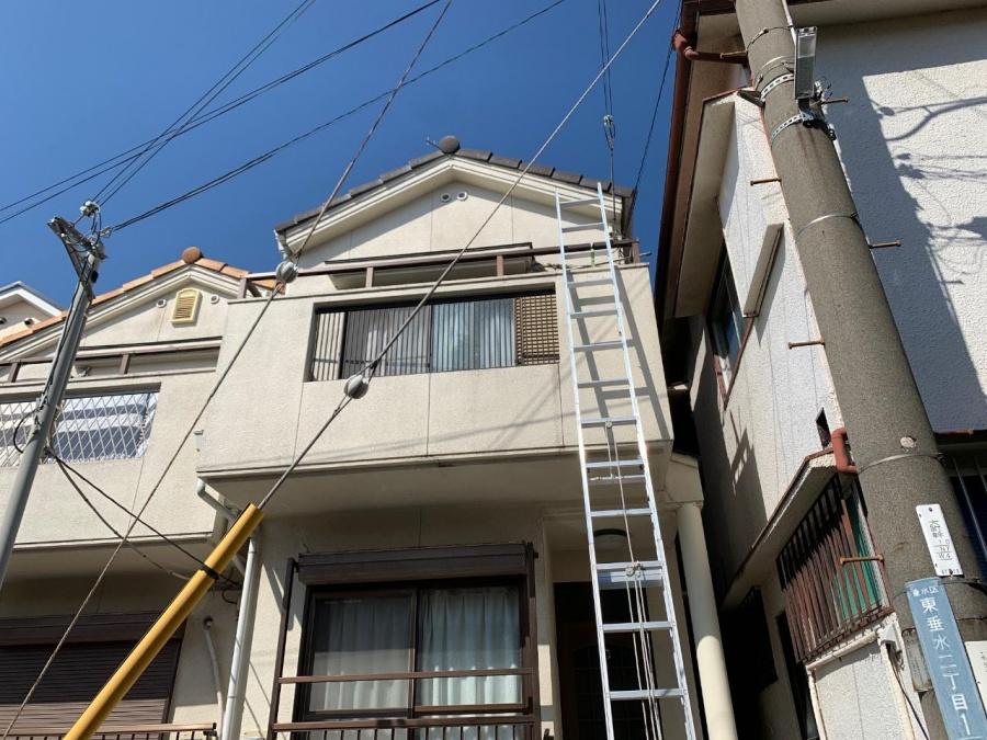 屋根に梯子を掛けている様子