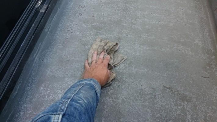 防水工事でトップコートを塗る前に葺き掃除している様子