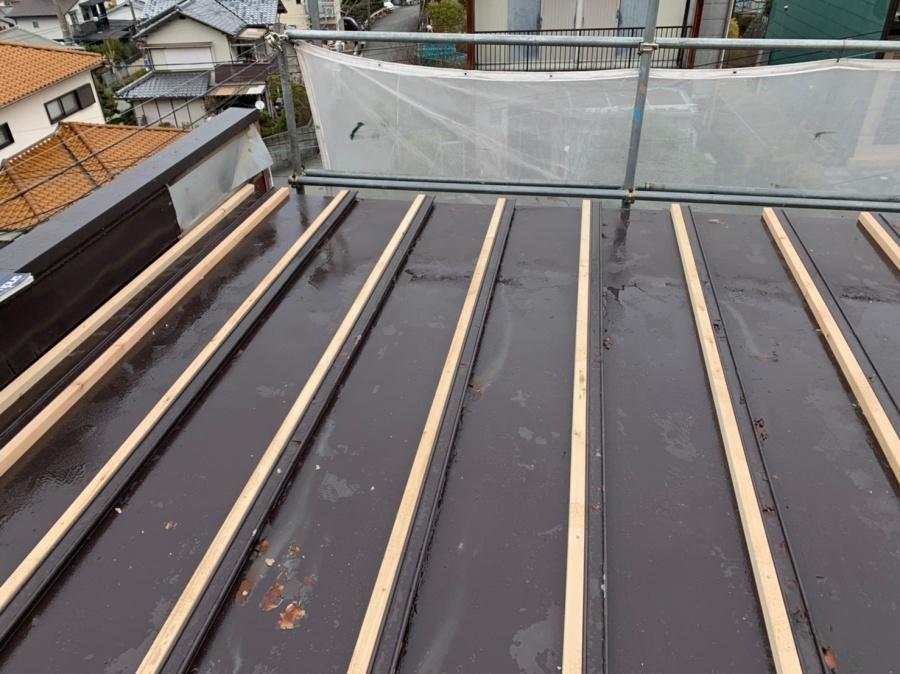 トタン屋根に垂木木材を取り付けている様子