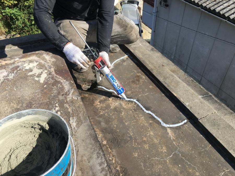 神戸市垂水区で行った屋上修理でひび割れ箇所にコーキングを塗っている様子