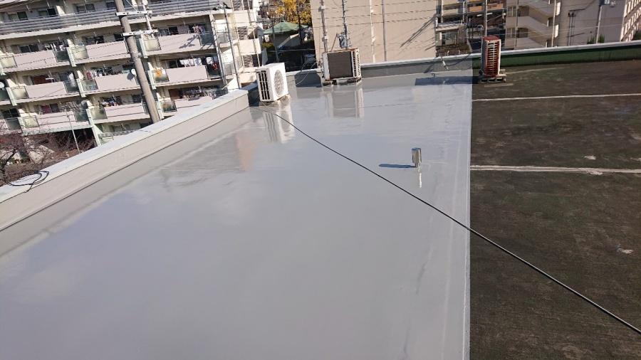 神戸市中央区で屋上防水工事でトップコートを塗っている様子