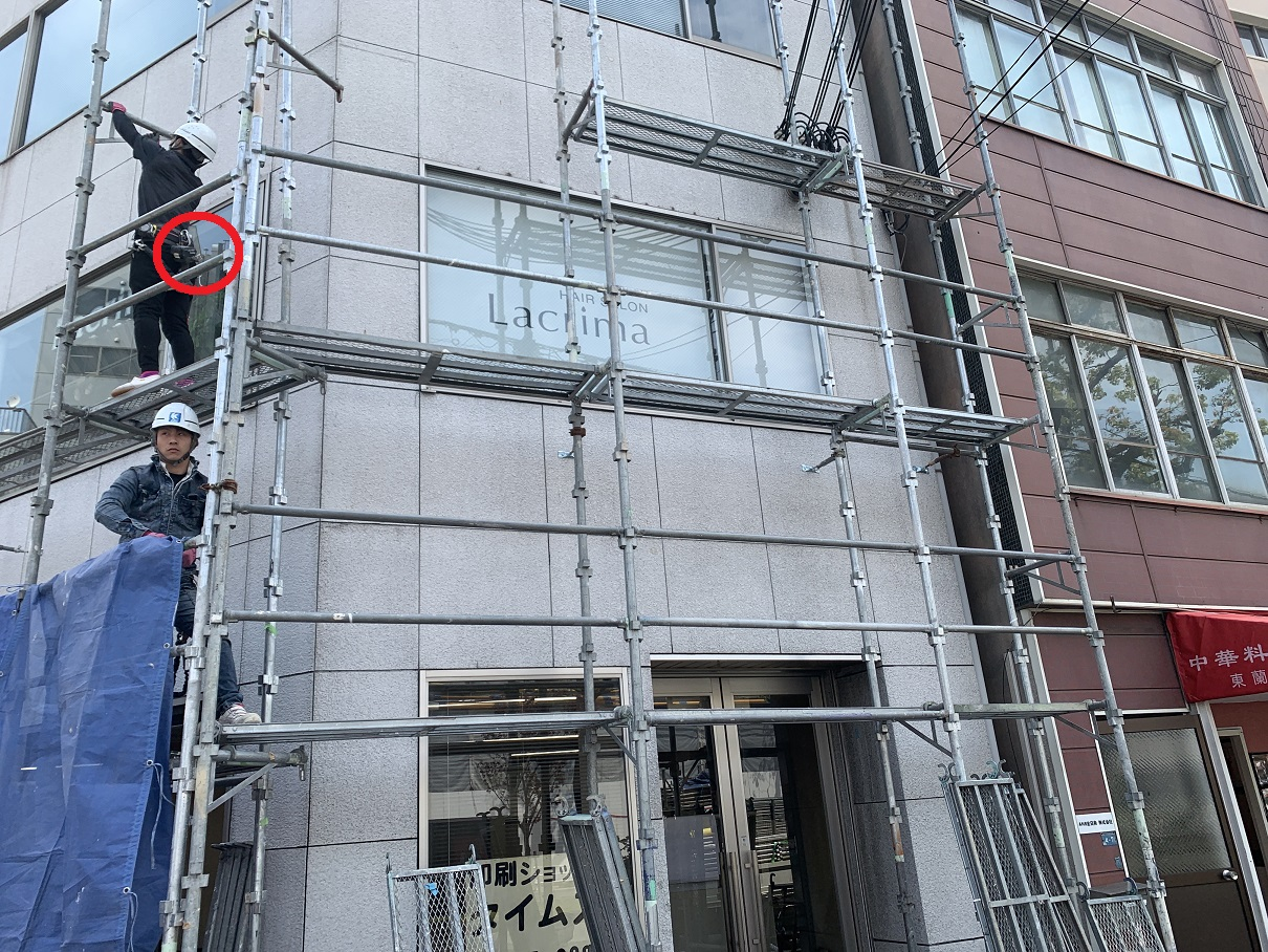 神戸市中央区での大規模修繕で足場を組む際に工具が落下しないように安全対策をしている様子