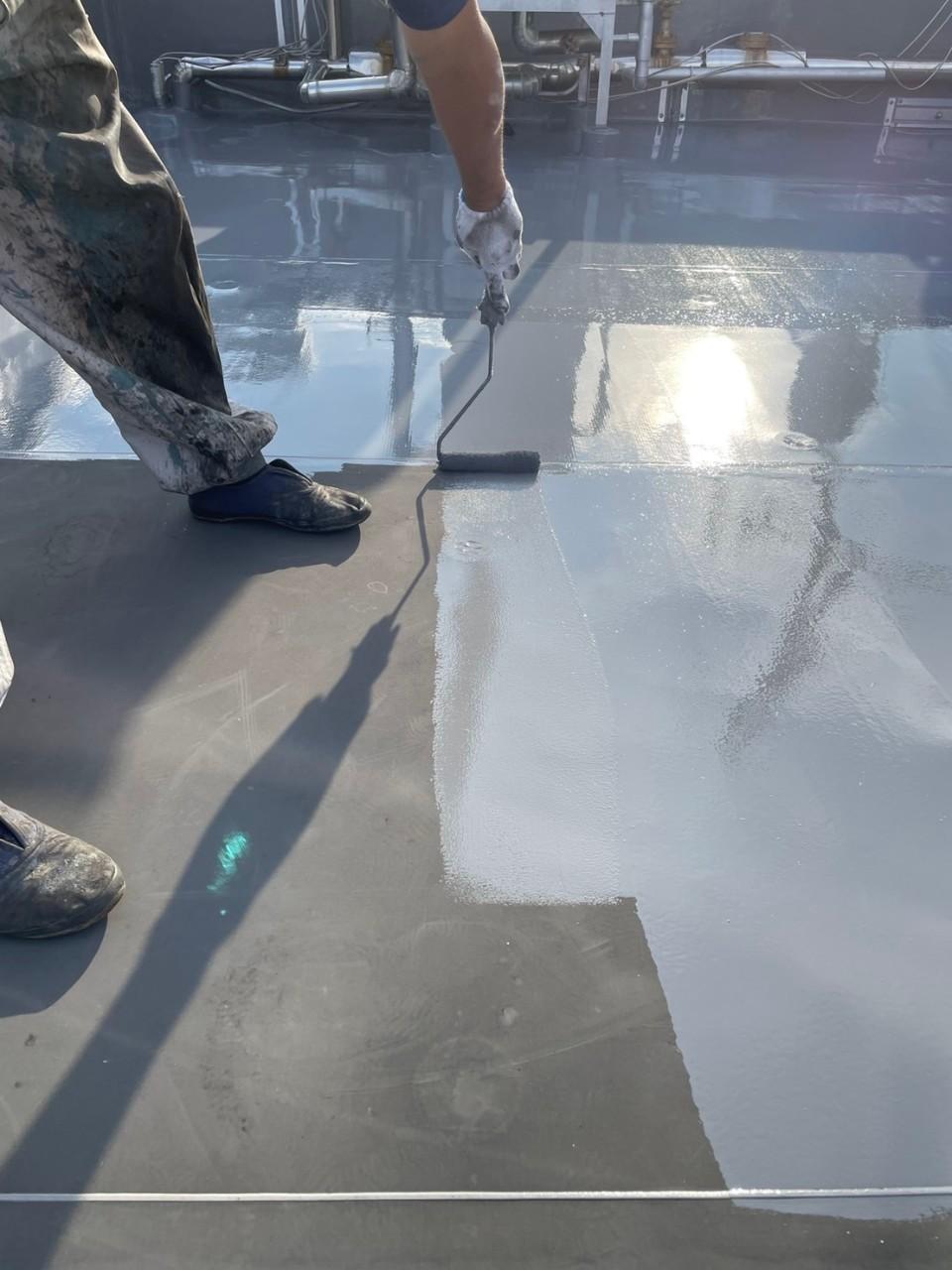 屋上のシート防水部分補修でトップコートを塗っている様子