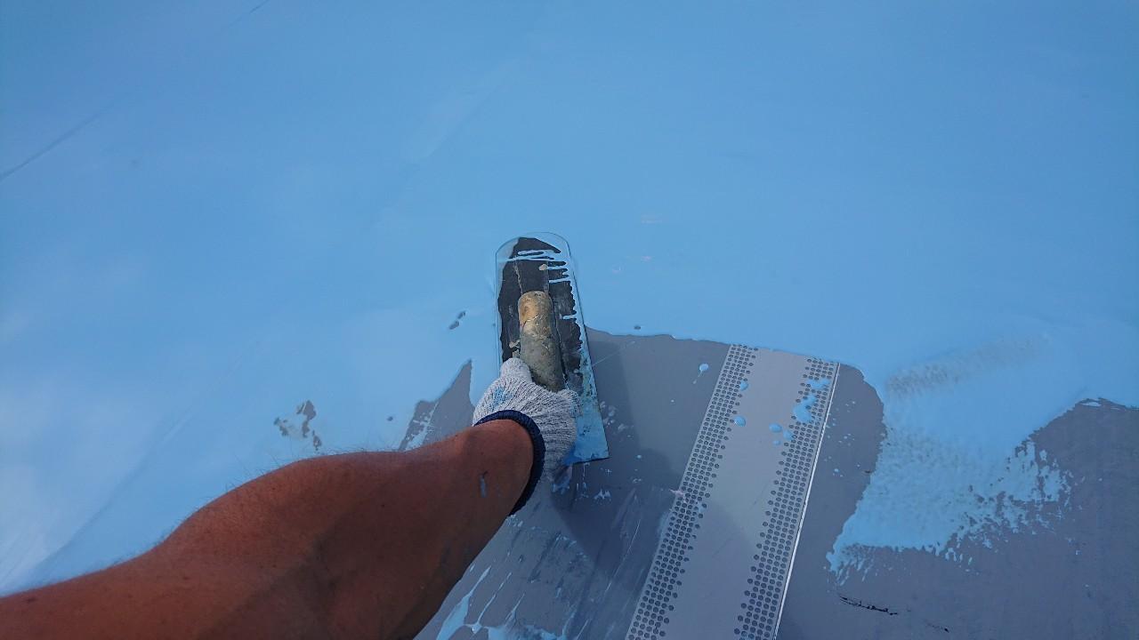 三木市での陸屋根防水工事で土間にウレタン防水を塗っている様子