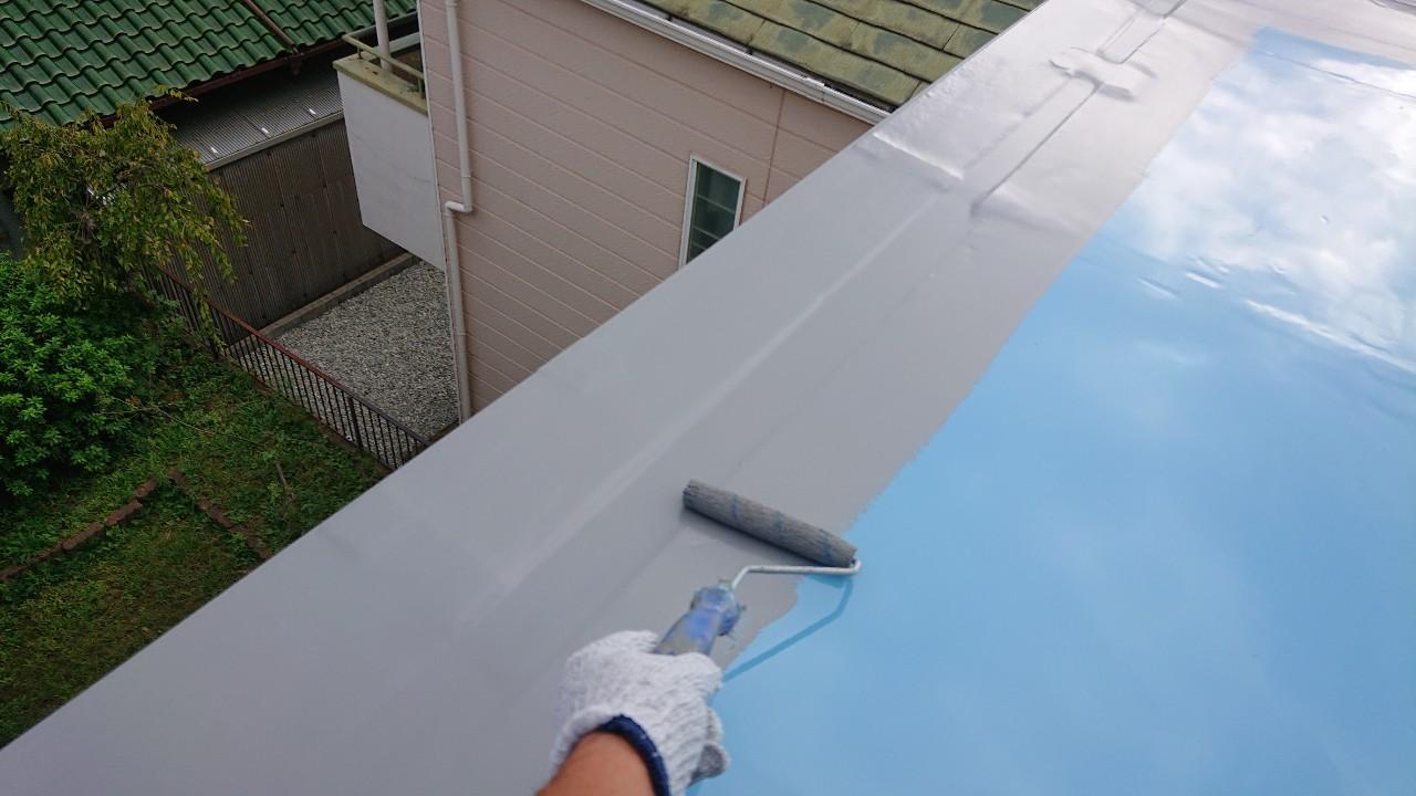 陸屋根防水工事で仕上げとなるトップコートを塗っている様子