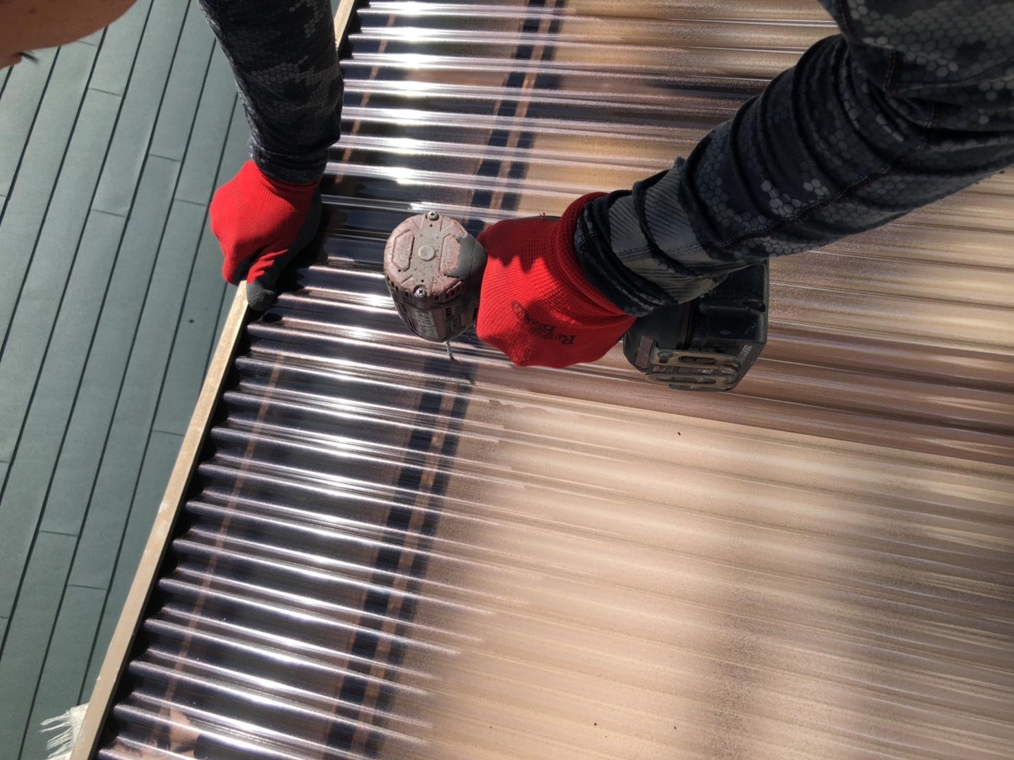 ベランダ屋根の波板を固定するために下穴を開けている様子