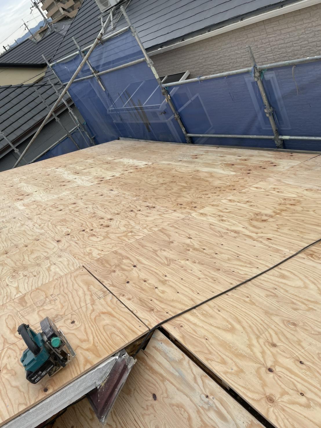 神戸市垂水区での屋根下地工事で下地用合板を切断し取り付けている様子