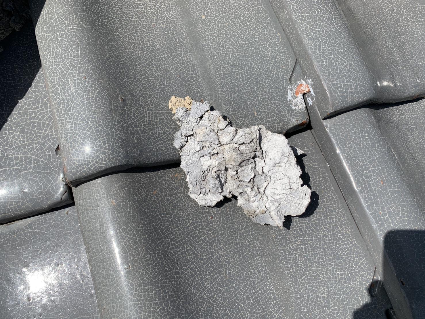劣化した漆喰が瓦屋根の上に転がっている様子