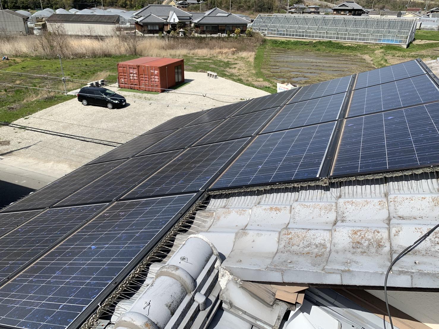 瓦屋根の上に太陽光パネルが乗っている様子