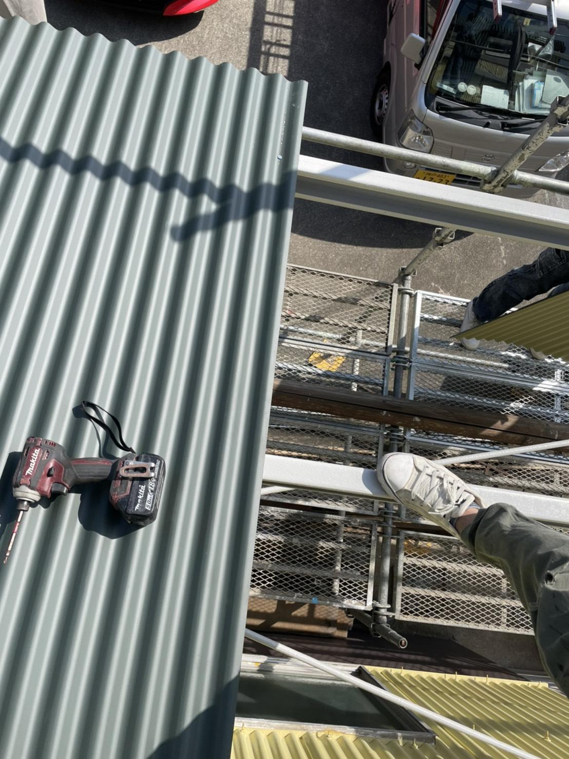 倉庫の庇にガルバリウム鋼板波板を貼っている様子