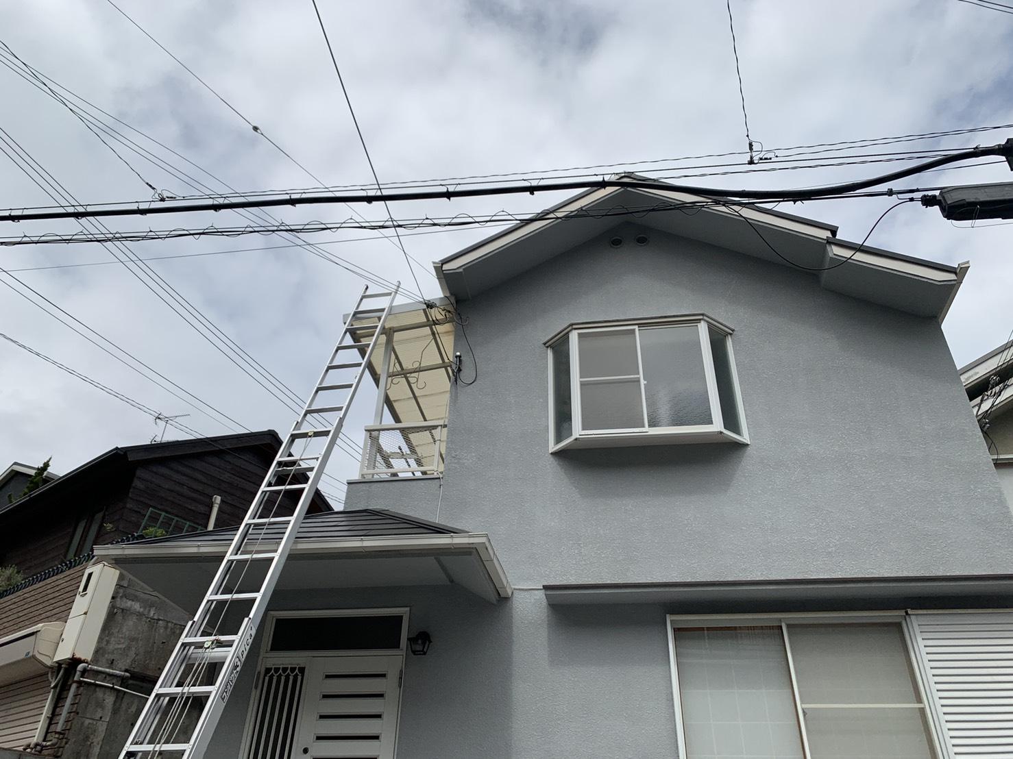 神戸市長田区での雨漏りの原因を調べるために屋根に梯子を掛けた様子