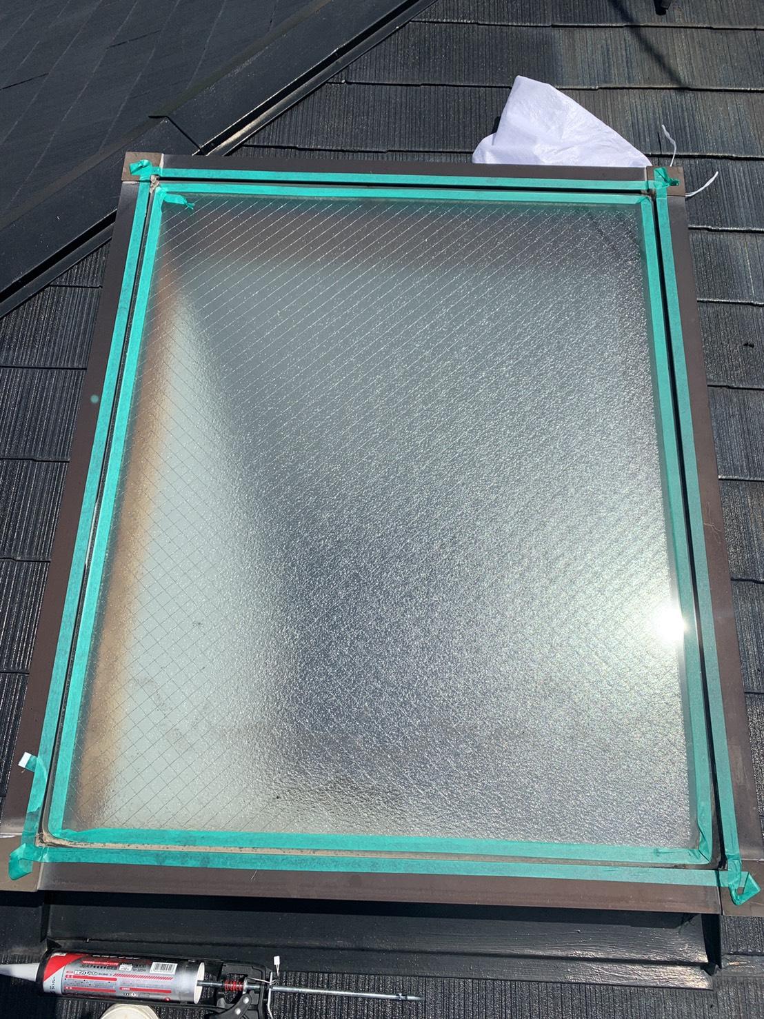 天窓ガラス廻りにマスキングテープを貼っている様子