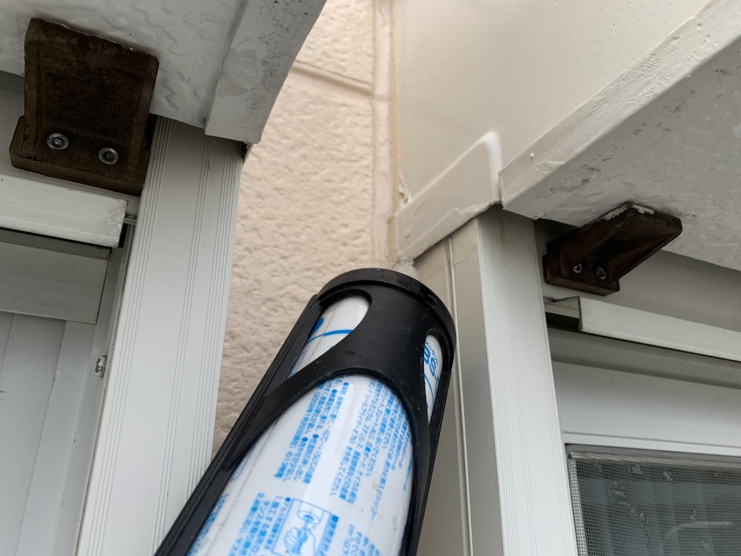 神戸市長田区の雨漏り補修で掃き出し窓のすき間にコーキングしている様子