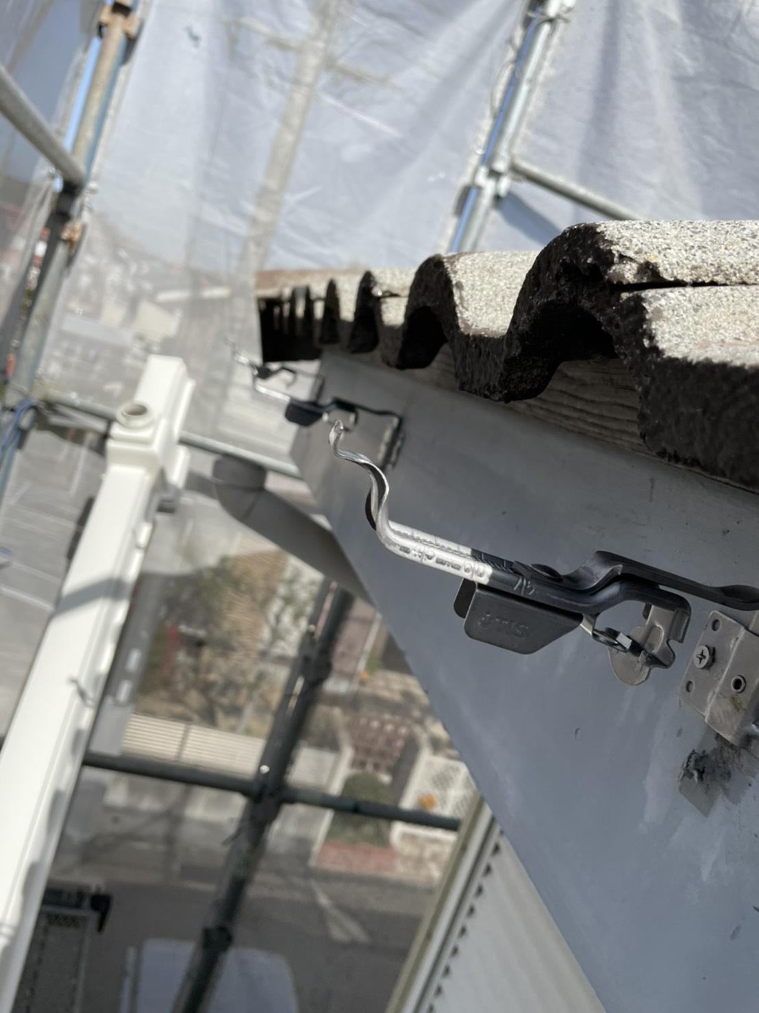 加古川市での雨樋交換でステンレスの受け金具を取り付けている様子