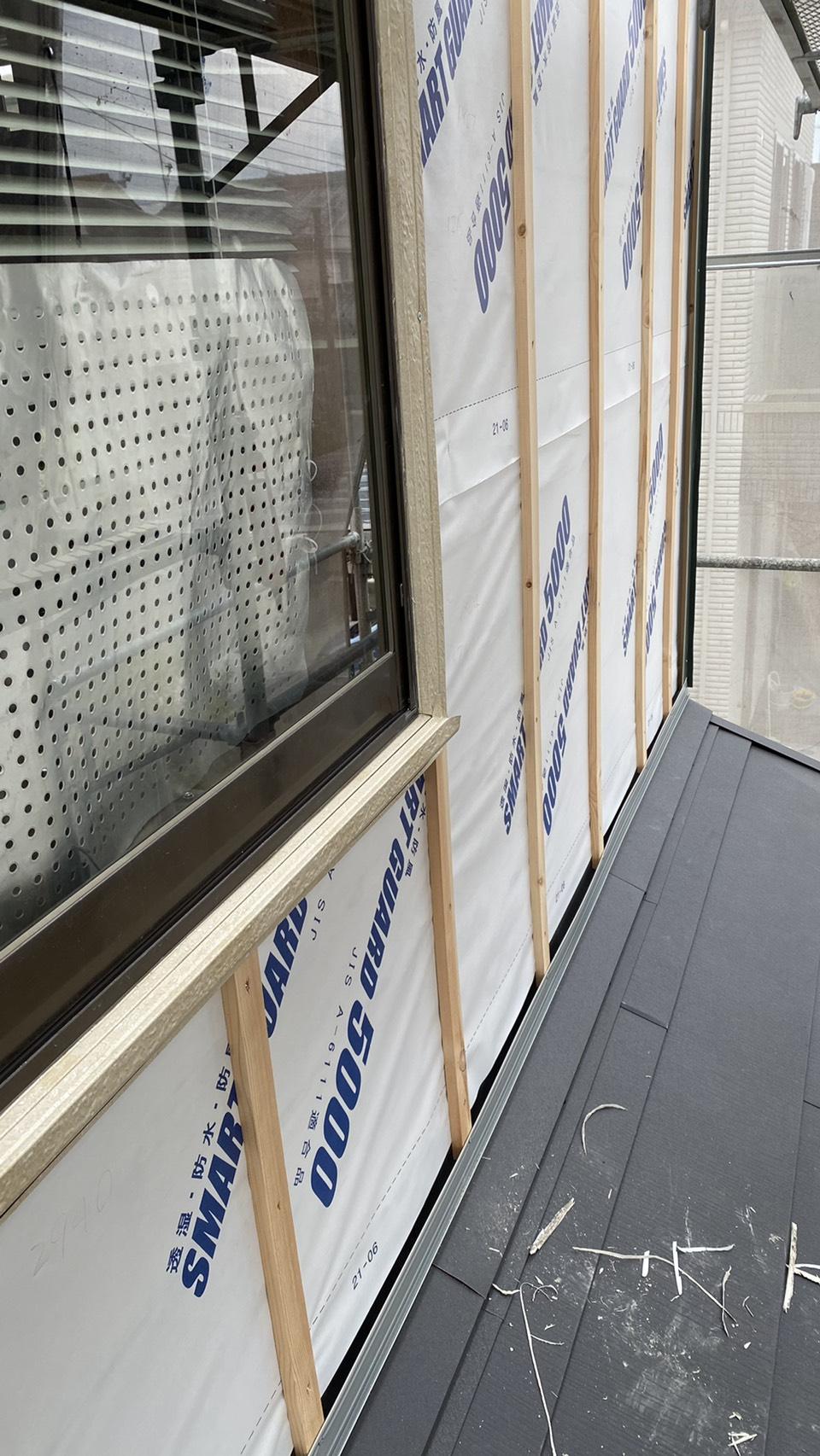 塗装不可な外壁に防水シートを貼っている様子