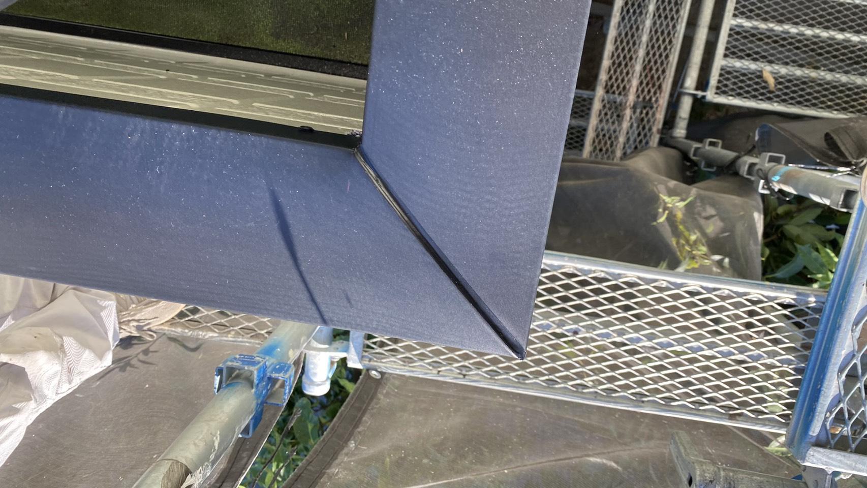 明石市でのベランダ笠木交換工事でステンレスの笠木を取り付けている様子