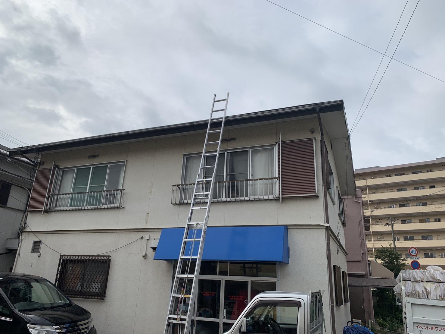 加古川市でスレート屋根からの雨漏りを調査するために梯子を屋根にかけている様子