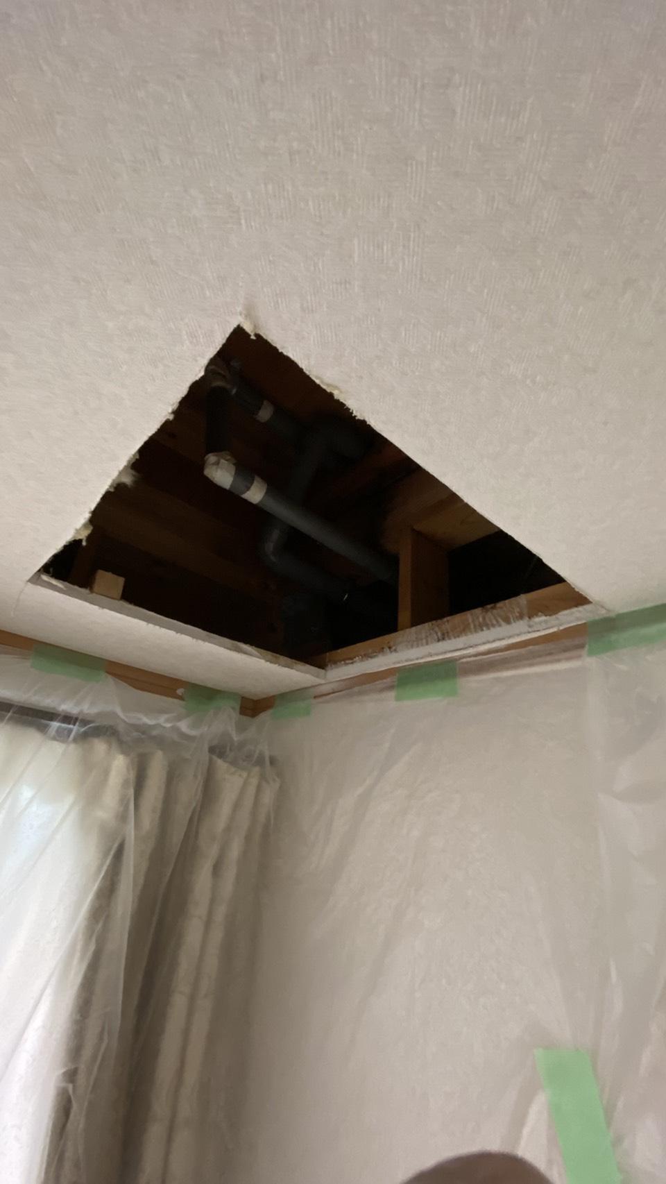雨漏りの原因となっている排水管を調査するために天井に開口を開けた様子