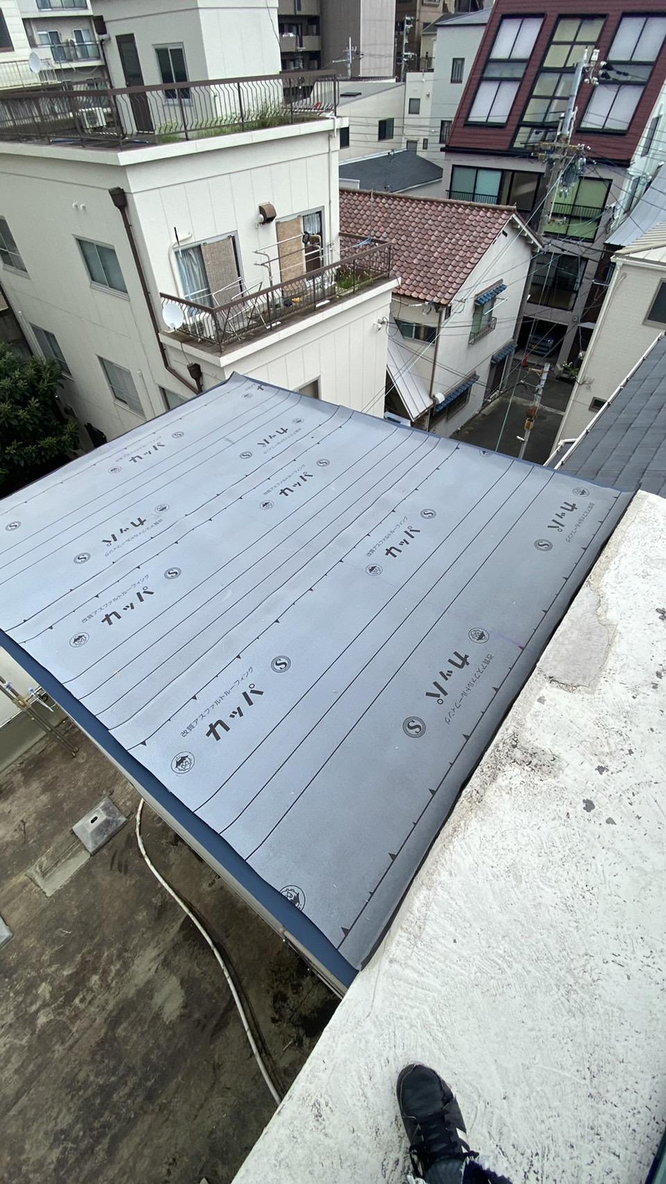 傾斜の緩い屋根に防水シートを貼った様子