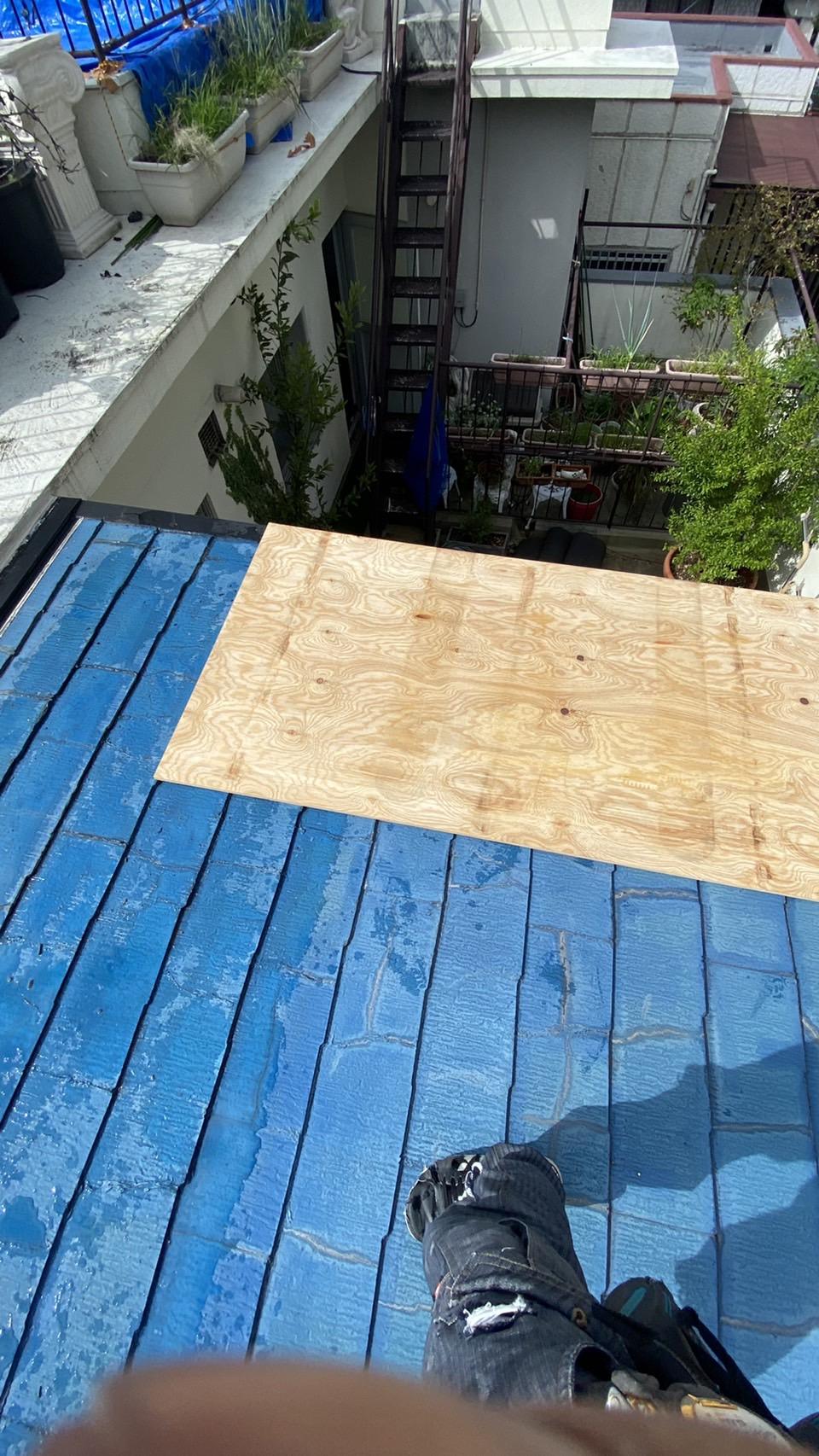 傾斜の緩い屋根に下地用合板を葺いている様子