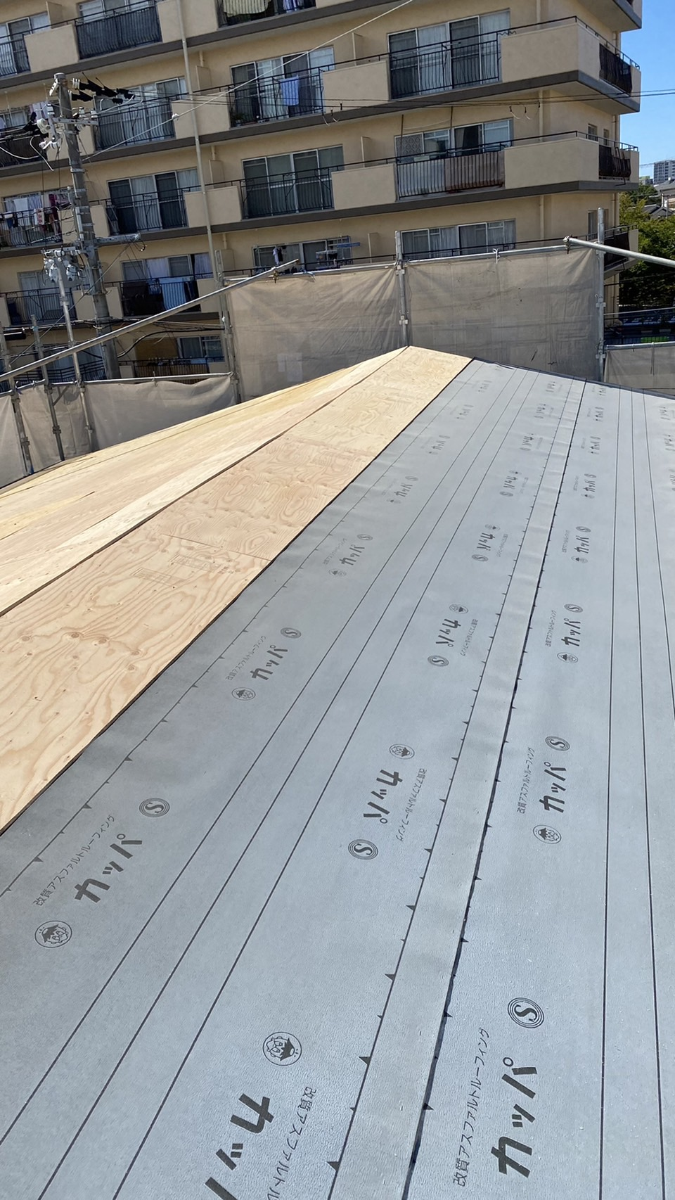 加古川市での屋根重ね葺き工事で防水シートを貼っている様子