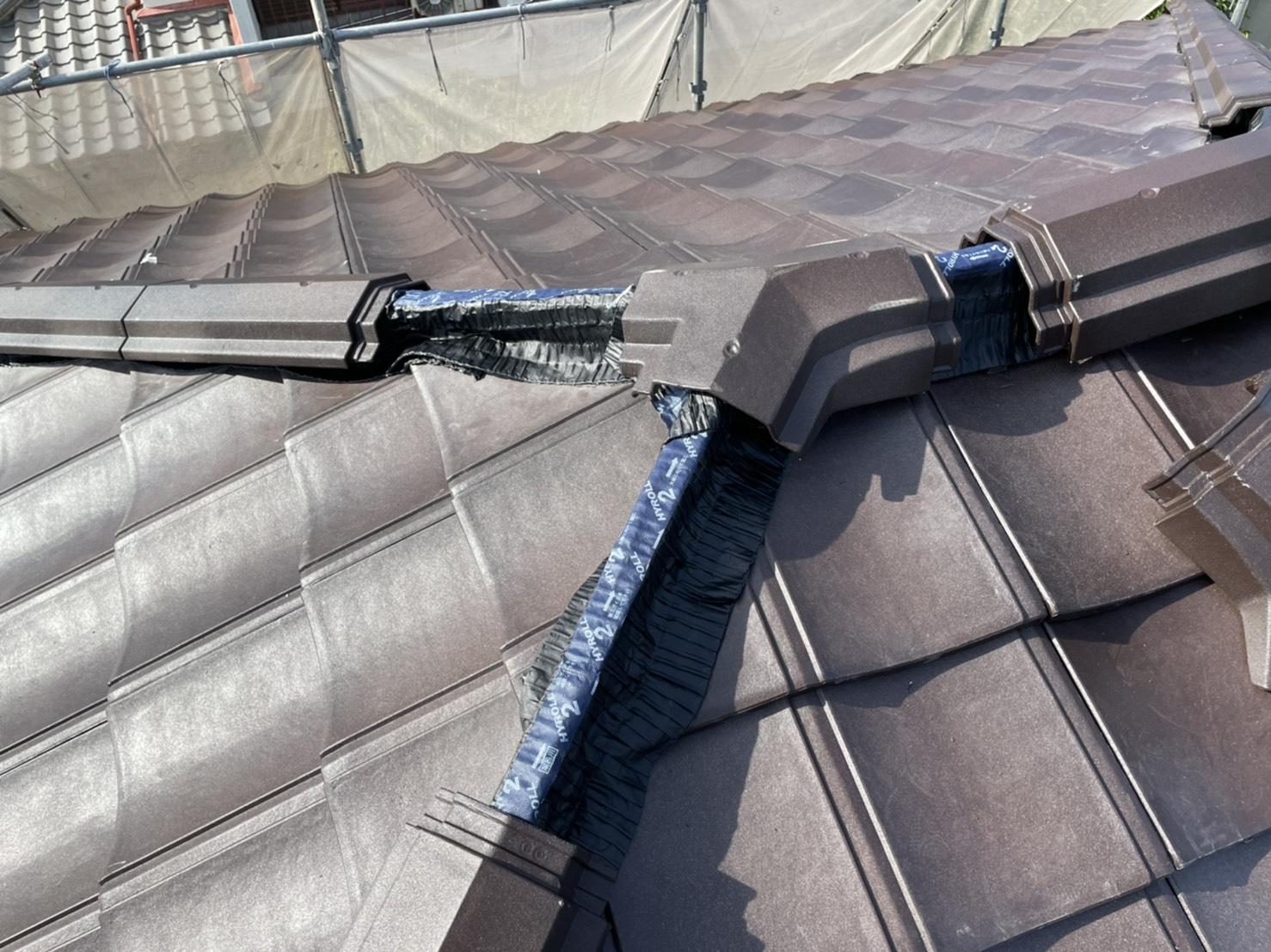 屋根葺き直し工事の仕上げにルーガの棟を取り付けている様子