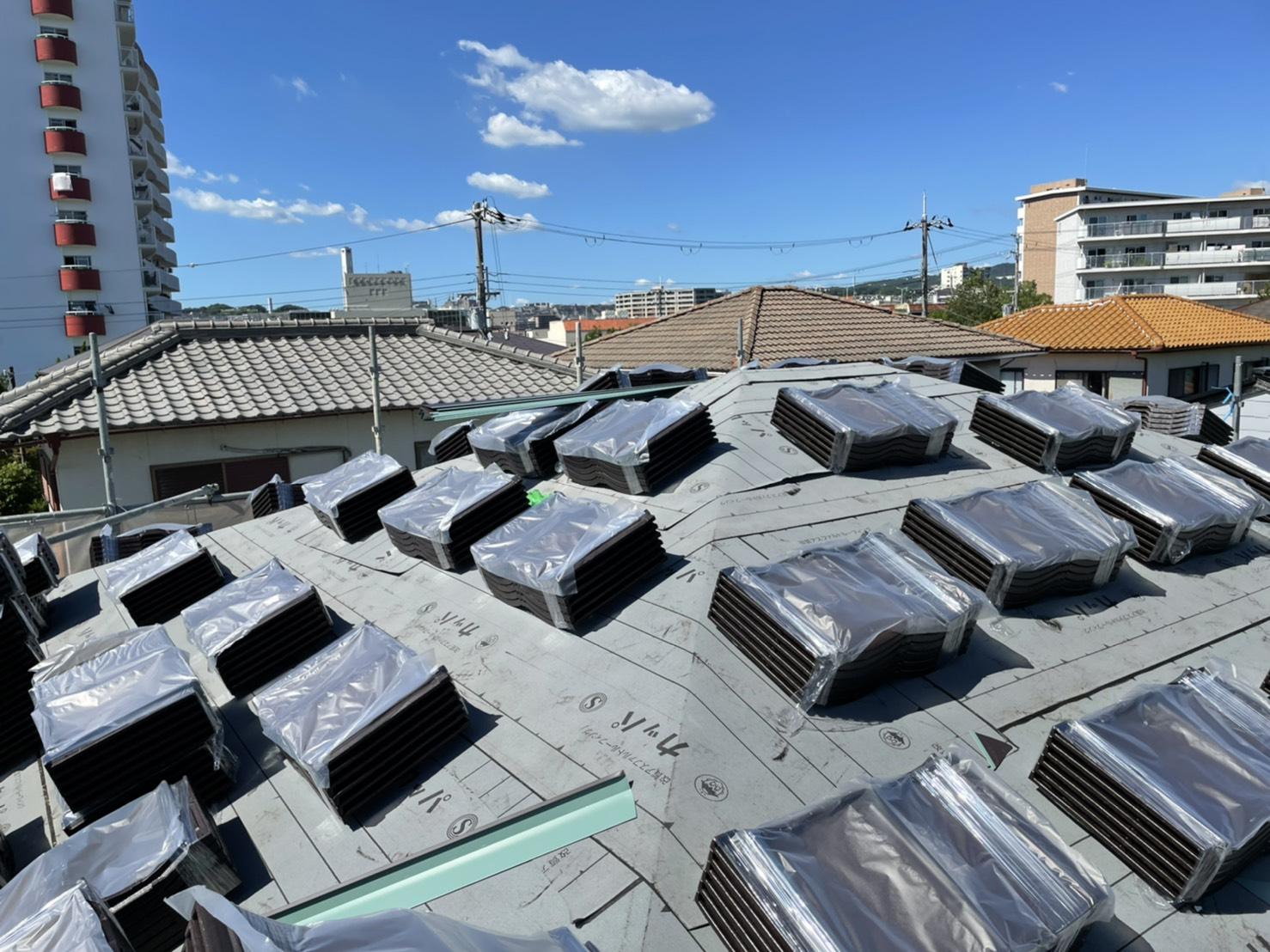 神戸市での屋根葺き直し工事でルーガを屋根に配っている様子