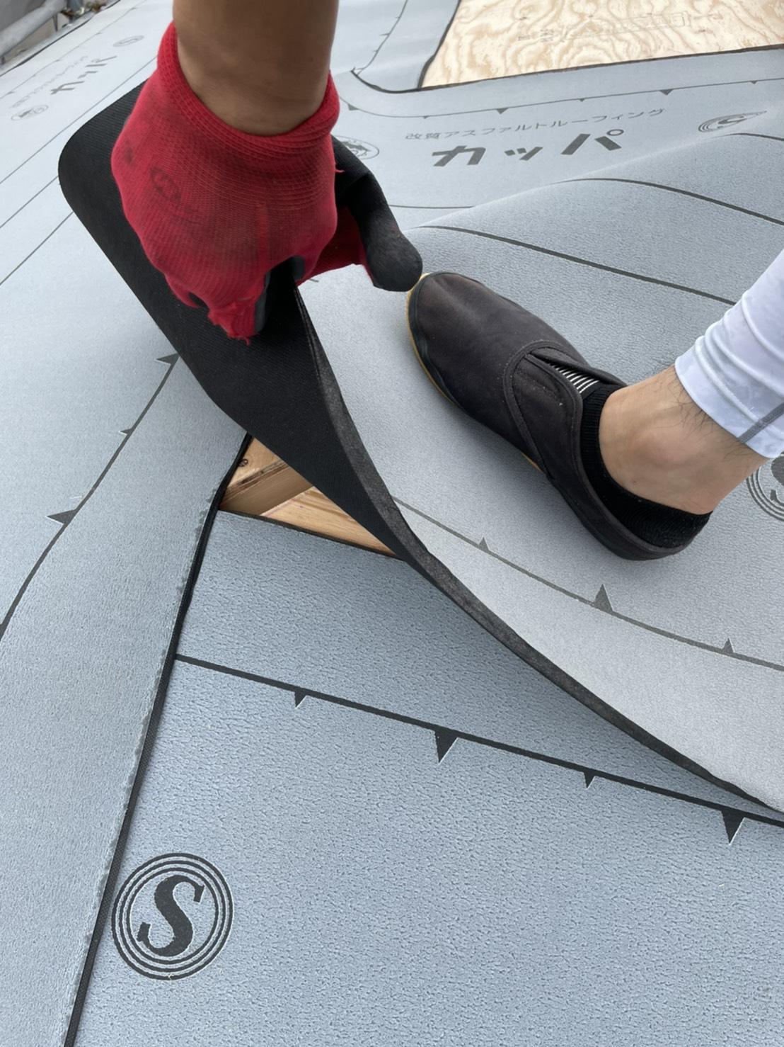 神戸市での雨漏りしている屋根葺き直し工事で防水シートを重ねている様子