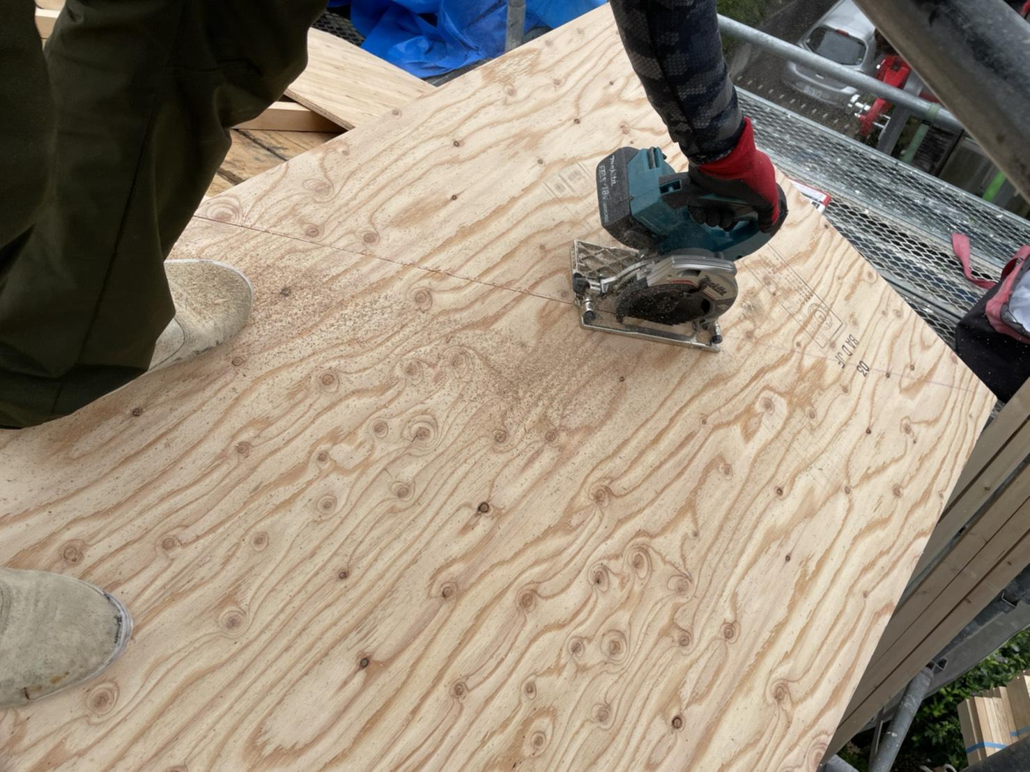 神戸市での雨漏りしている屋根葺き直し工事で下地用合板を切断している様子
