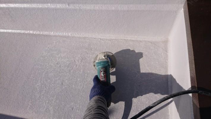 三木市での防水リフォーム工事でグラインダーを使用してけれんしている様子