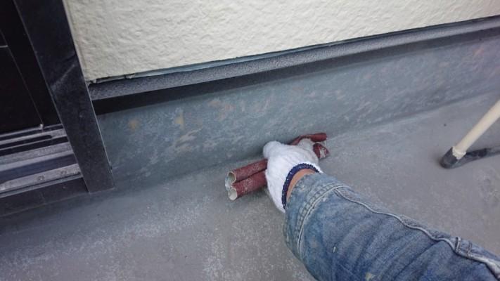 防水工事でトップコートを塗る前にケレンしている様子