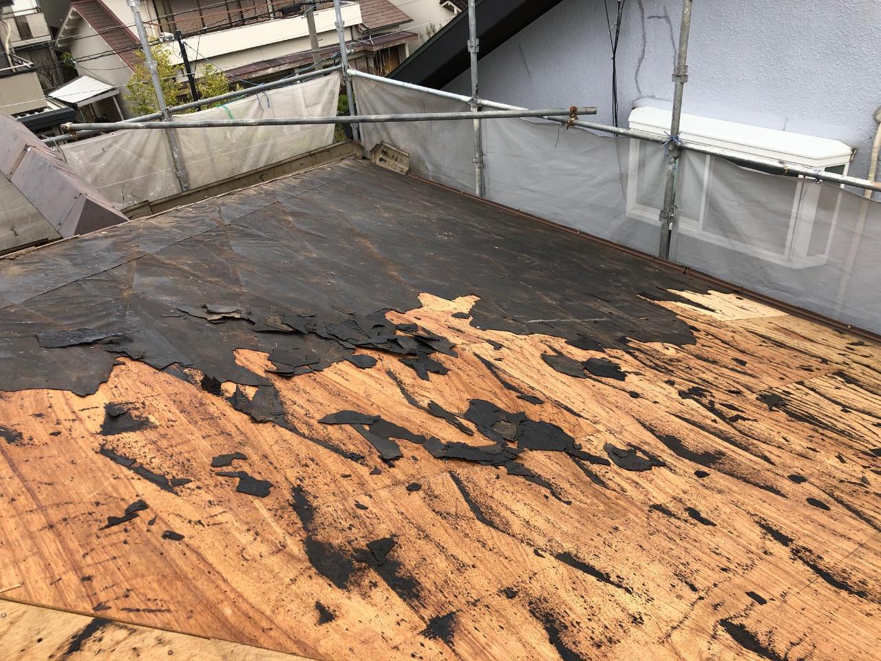 屋根葺き替え工事で既存の防水シートを撤去している様子