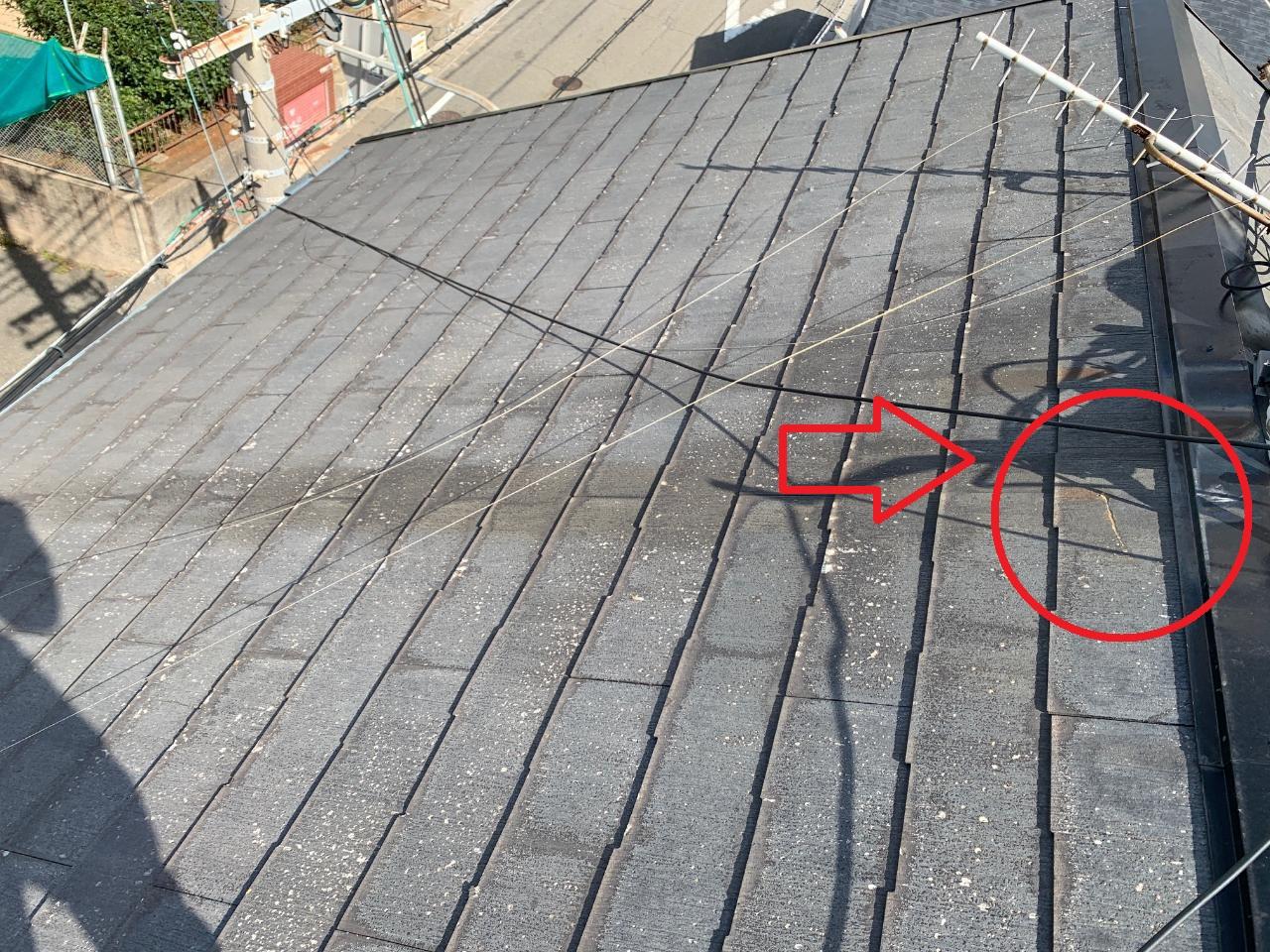 台風により屋根上のアンテナが倒壊してスレート屋根がひび割れている様子